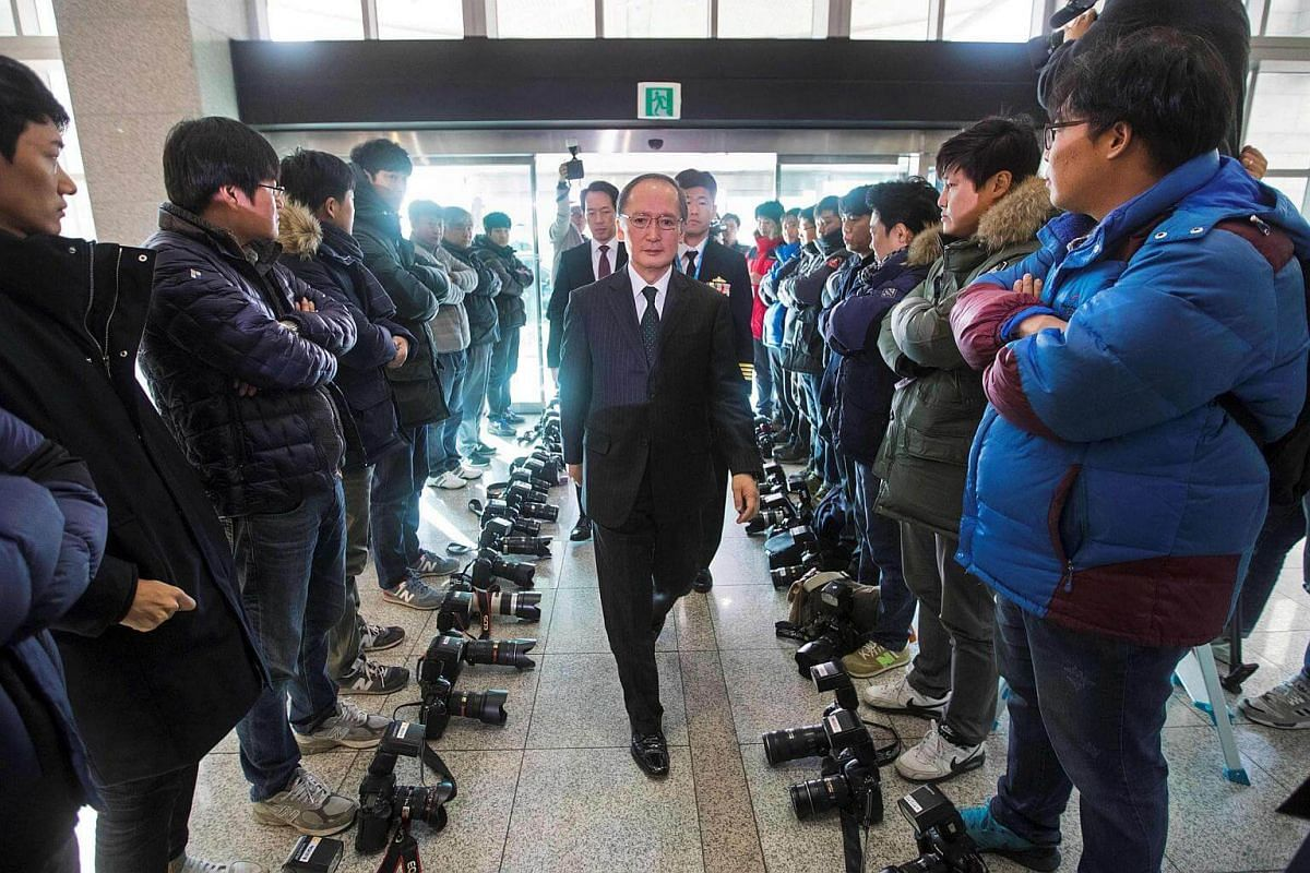 South Korean photographers lay their cameras on the ground in protest against the defence ministry's decision not to allow them to take pictures of the signing of a South Korea-Japan military intelligence exchange treaty as Japanese Ambassador to Seo