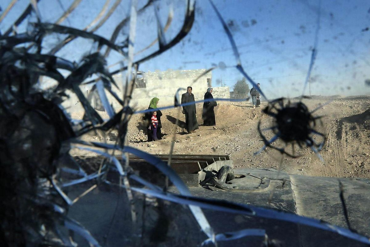 A picture taken through the bullet-riddled windshield of an Iraqi Special Forces armoured vehicle shows residents walking on a street in the Aden district of Mosul after troops almost entirely retook the area from ISIS soldiers on Nov 22, 2016.