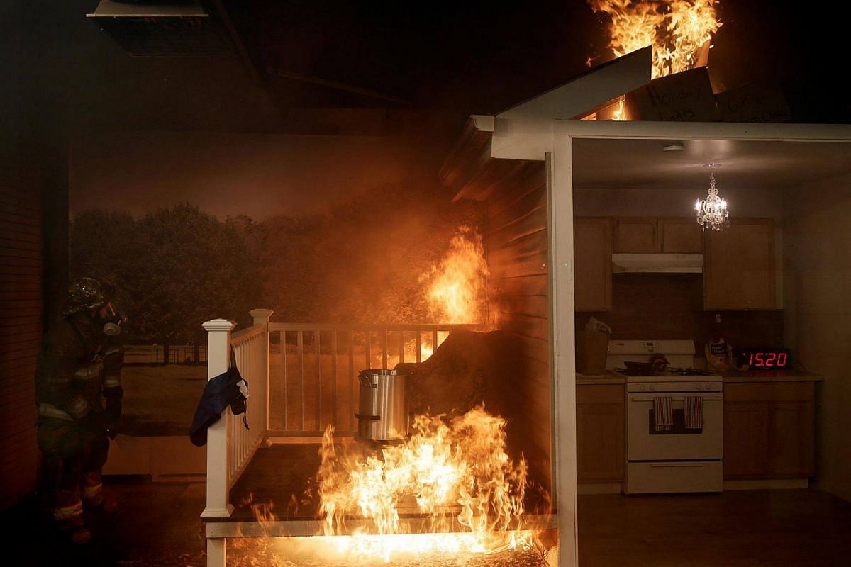 A firefighter (left) attempts to put out a fire after a frozen turkey was dropped into a hot deep fryer at a Consumer Product Safety Commission Thanksgiving fire and food safety demonstration of holiday kitchen fires in Rockville, Maryland, US, on No