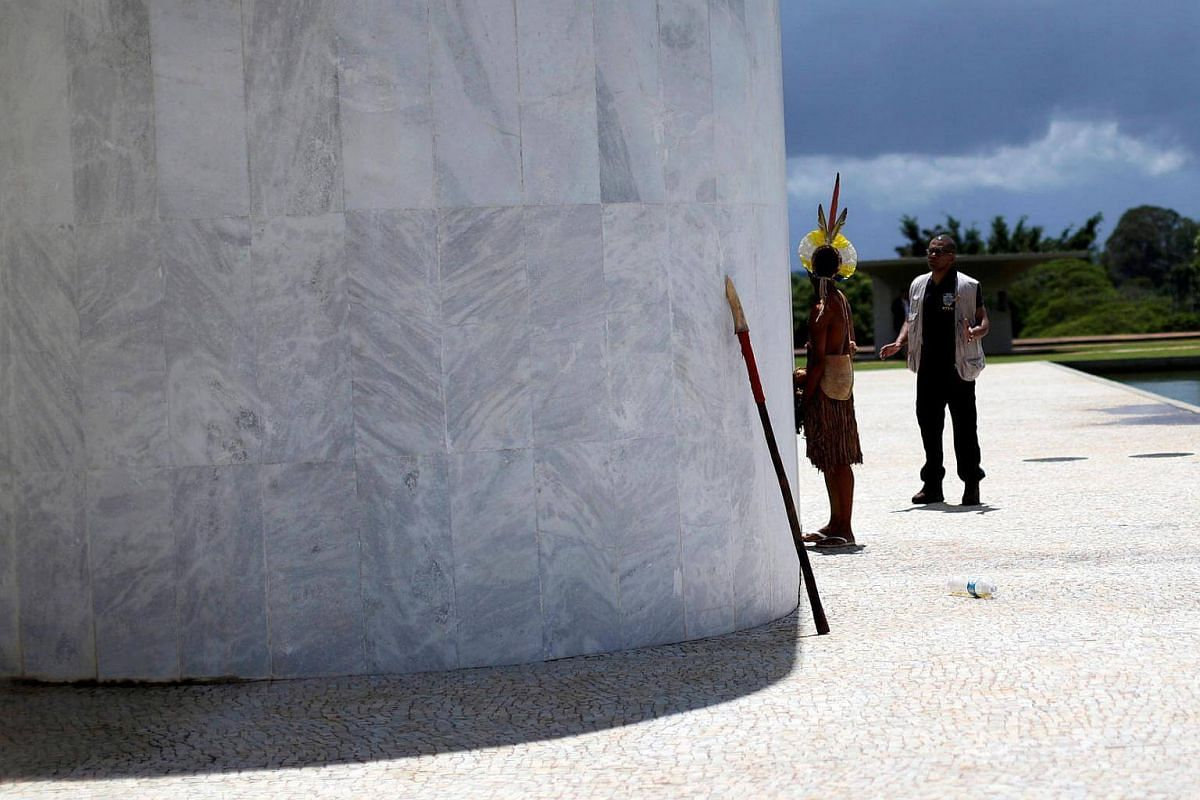 A security officer tries to prevent Indians from urinating on the wall of the parlor in front of the Planalto Palace during a protest of indigenous people from various tribes against agribusinesses and in demand of the demarcation of their ancestral