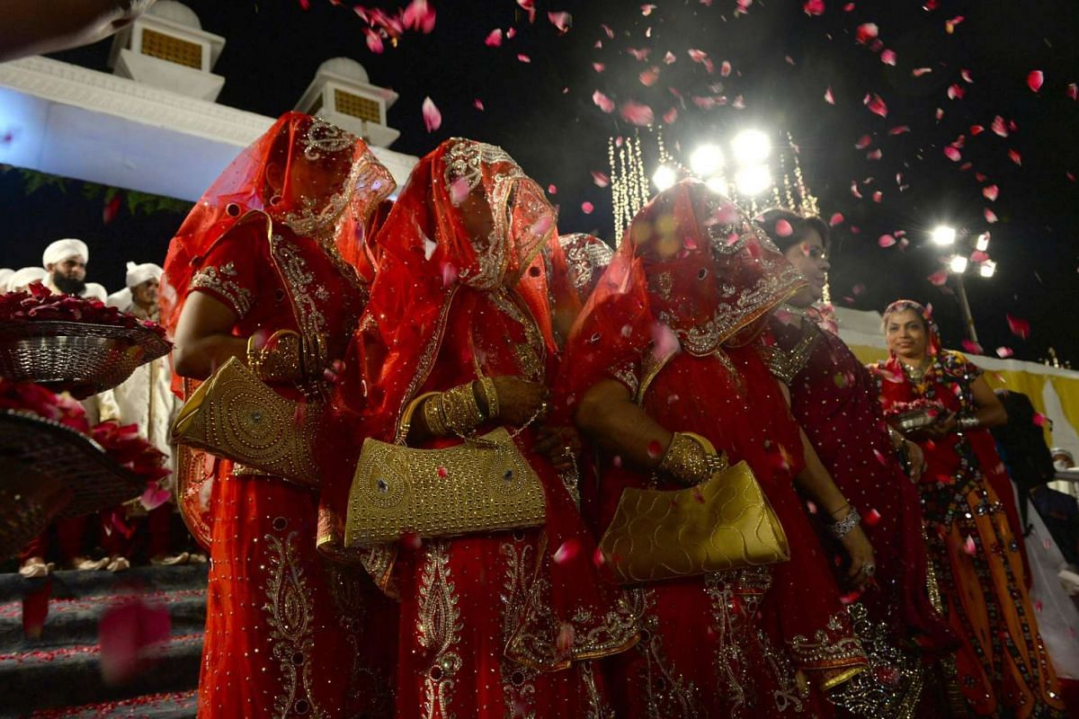 Ushers shower rose petals on Indian Muslim brides as they arrive for a mass marriage in Mumbai on Nov 23, 2016.