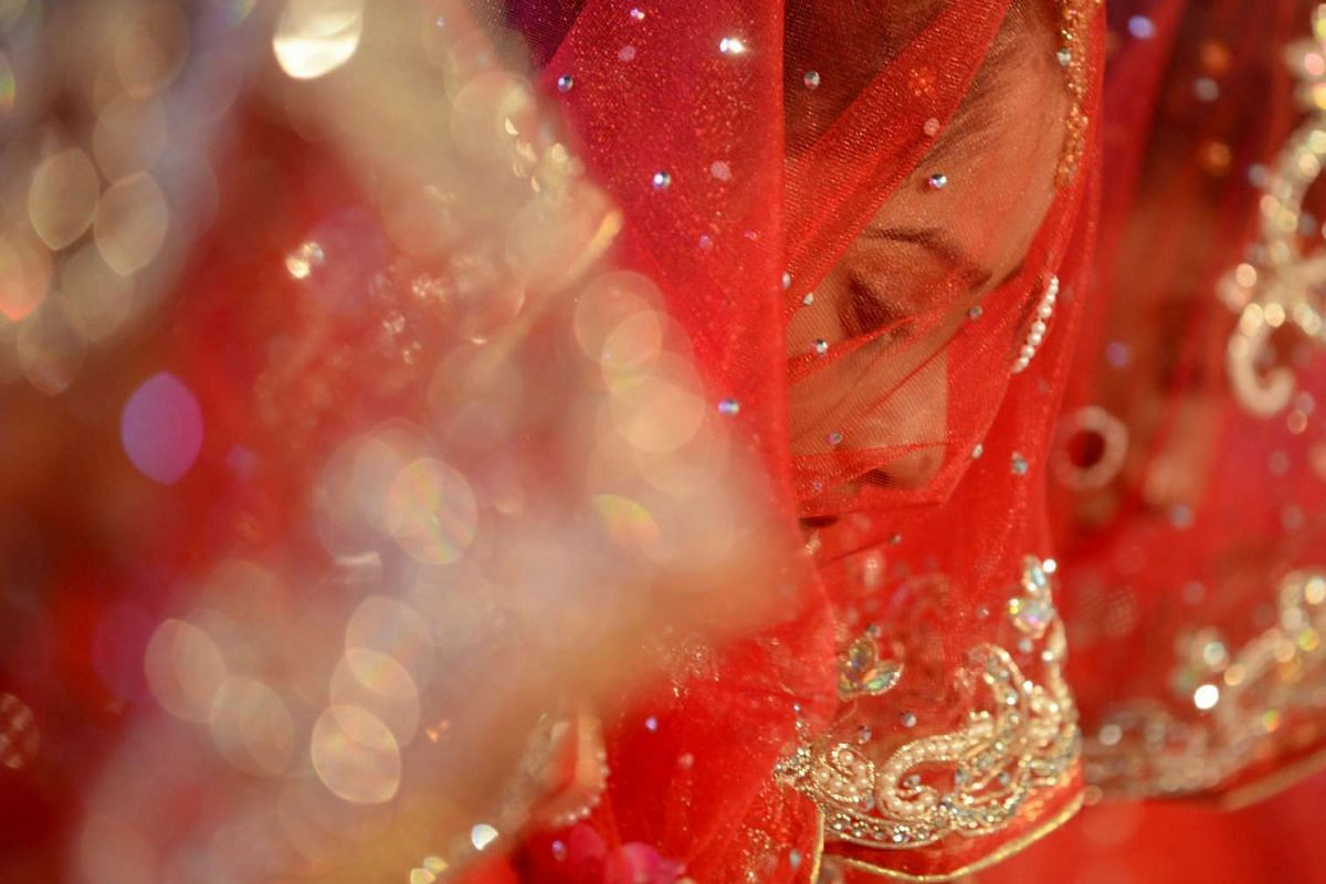 An Indian Muslim bride is seen through her veil at a mass marriage in Mumbai, on Nov 23, 2016.