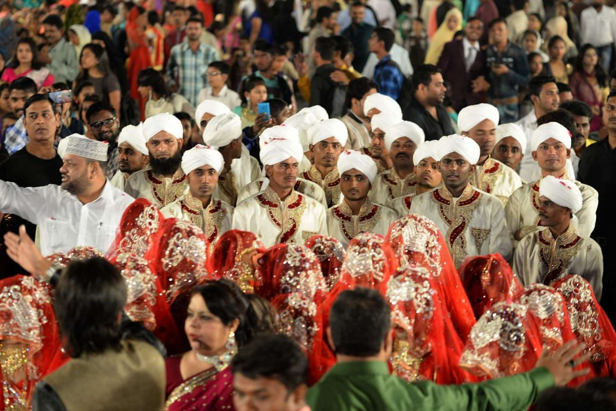 Indian Muslim grooms stand behind their brides as they arrive for a mass marriage in Mumbai on Nov 23, 2016.