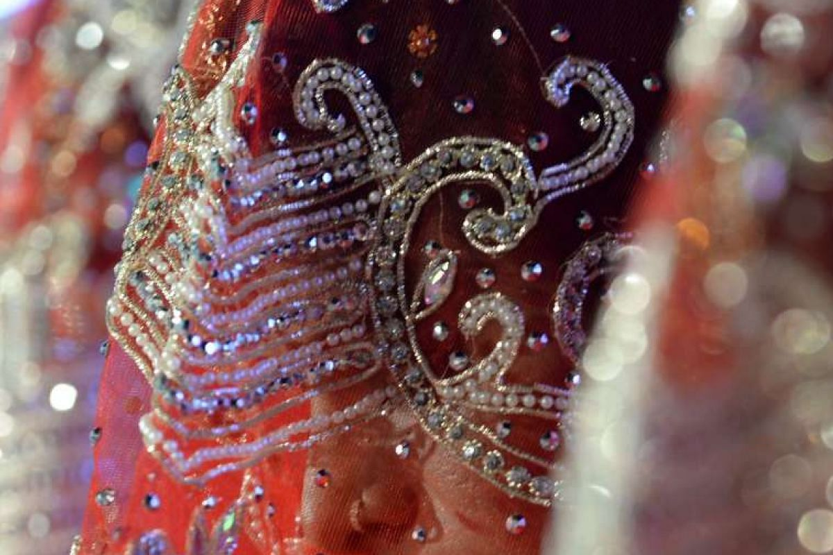Dressed in traditional marriage attire, an Indian Muslim bride is seen through her veil at a mass marriage in Mumbai on Nov 23, 2016.