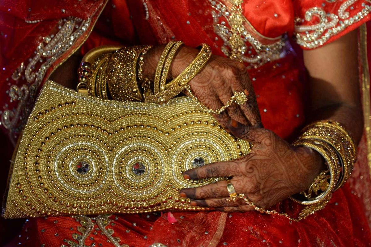 An Indian Muslim bride holds her purse at a mass marriage in Mumbai on Nov 23, 2016.