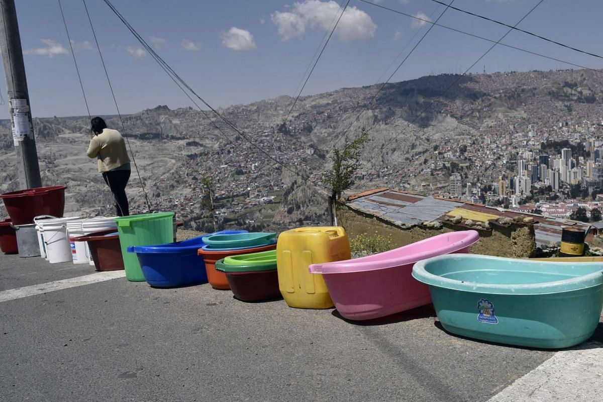Inhabitants of a neighbourhood queue with empty buckets to wait for a water supply tanker, in La Paz on Nov 23, 2016
