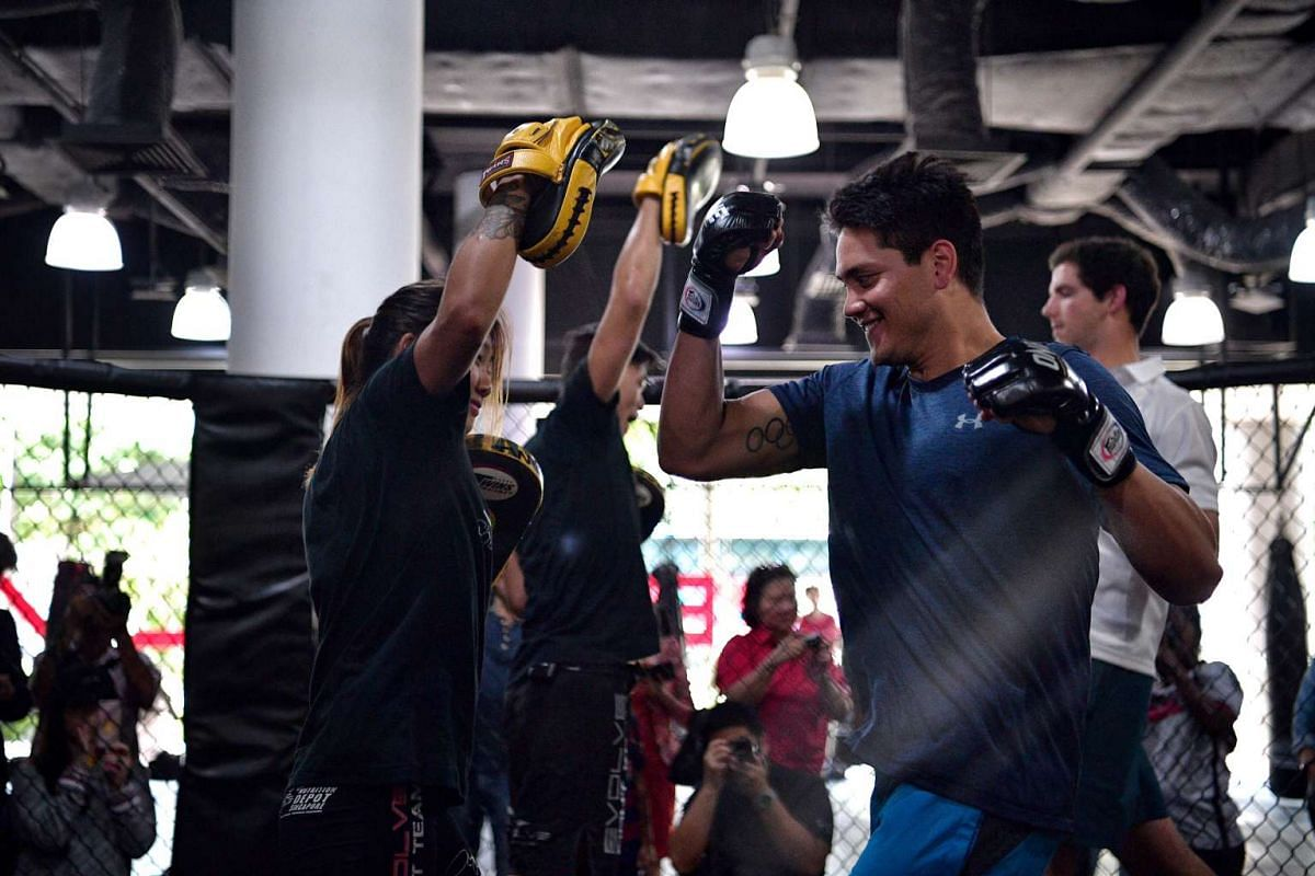 Joseph Schooling (right) being given an MMA crash course by One Championship atomweight champion Angela Lee (left) at Evolve MMA on Nov 24, 2016.