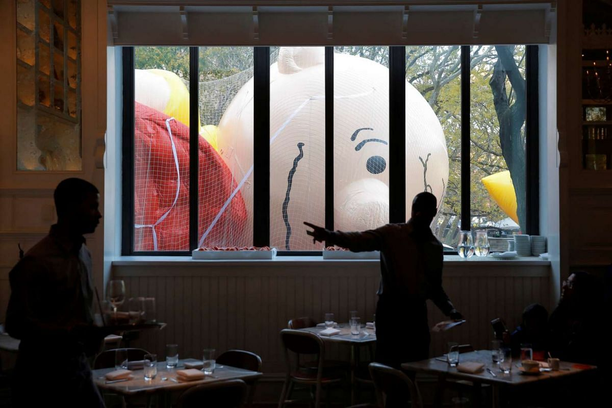 Wait staff work in the Storico restaurant beside the inflated Charlie Brown balloon ahead of the 90th Macy's Thanksgiving Day Parade in Manhattan, New York on Nov 23, 2016.