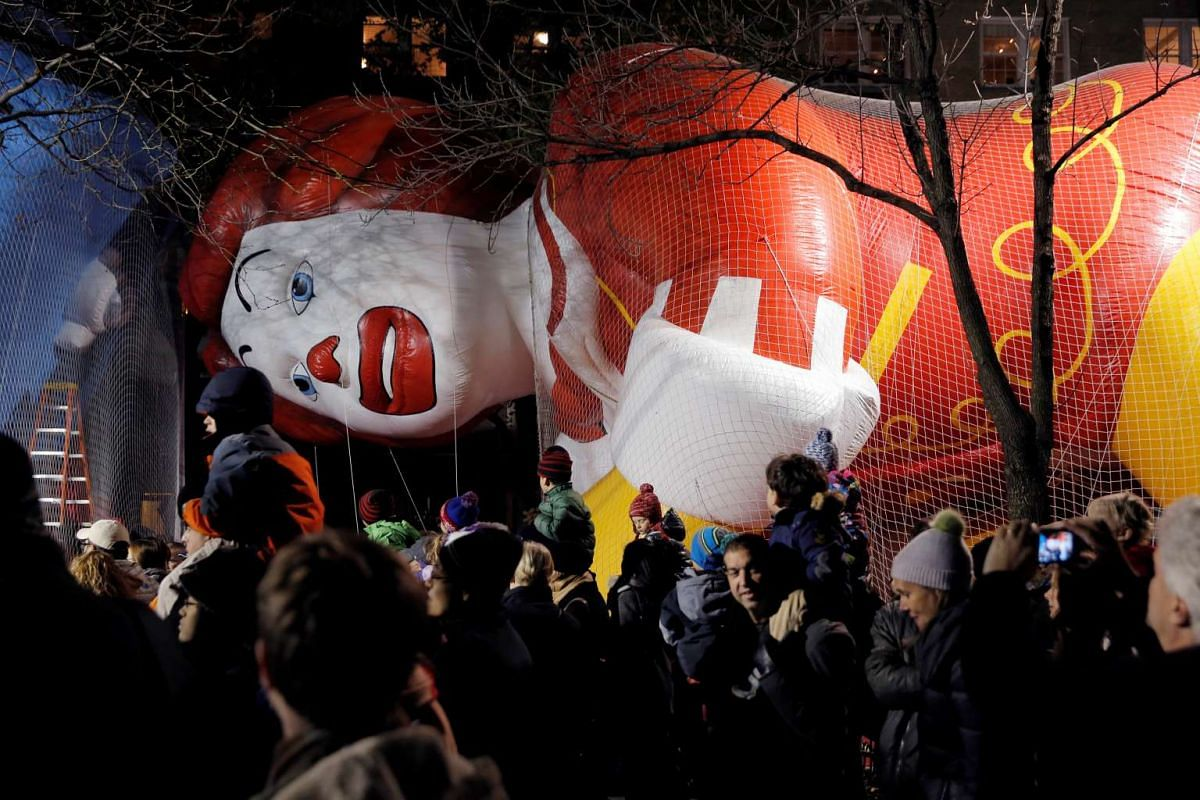 Crowds walk by the Ronald McDonald balloon ahead of the 90th Macy's Thanksgiving Day Parade in Manhattan, New York on Nov 23, 2016.