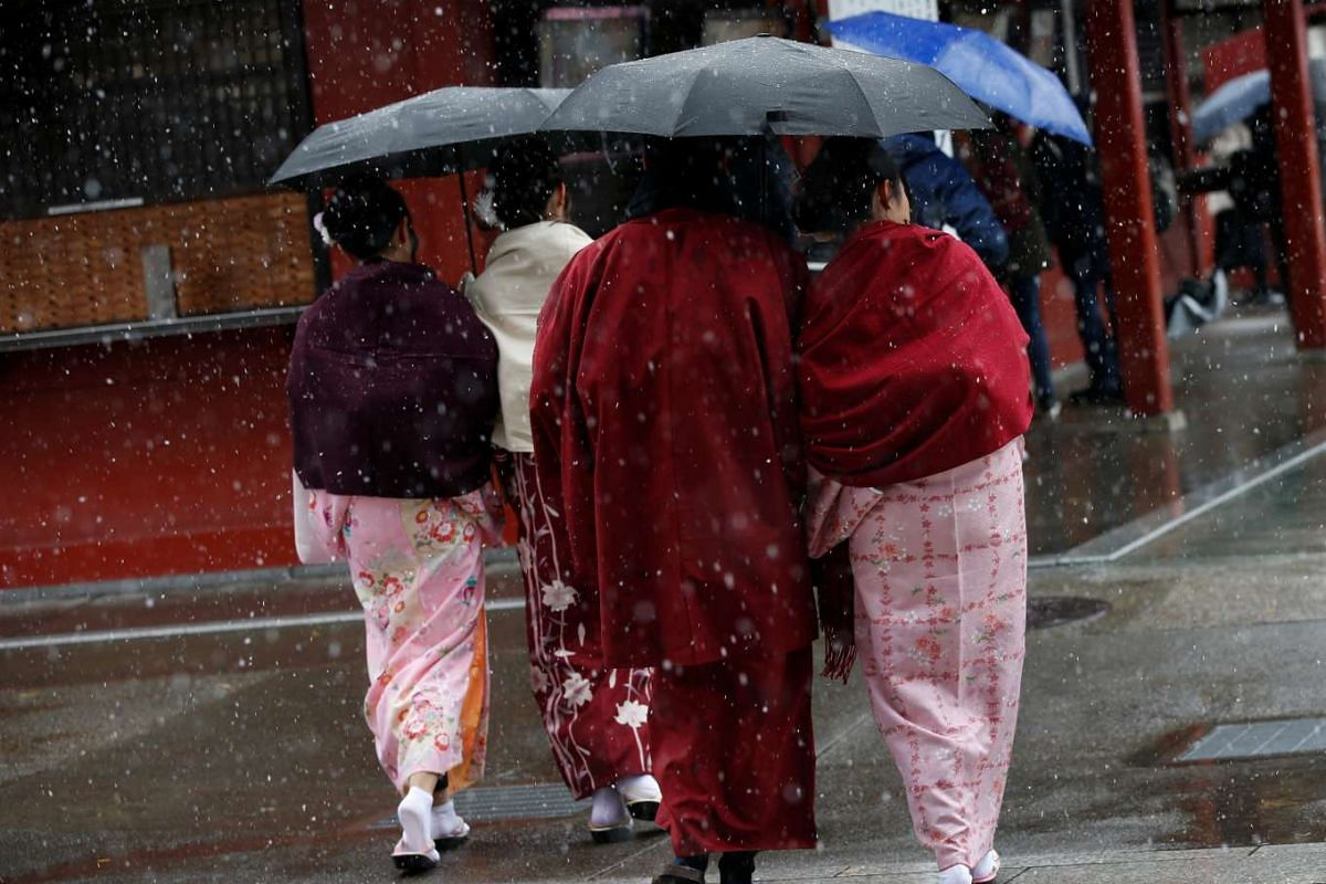 People in kimonos walk during the first November snowfall in 54 years at Senso-ji Temple in Tokyo, on Nov 24, 2016.