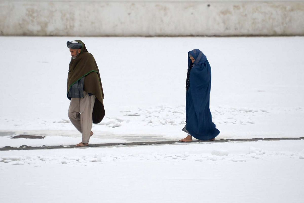 An Afghan couple walk through the snow in the courtyard of the the famous Blue Mosque in Mazar-i-sharif on Nov 24, 2016.