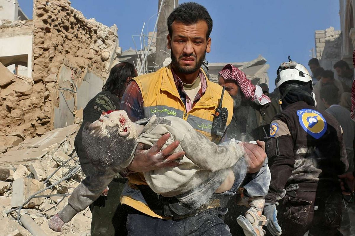 A Syrian medic carries the body of a boy after it was retrieved from the rubble following a reported barrel bomb attack on the Bab al-Nairab neighbourhood of Aleppo on Nov 24, 2016.