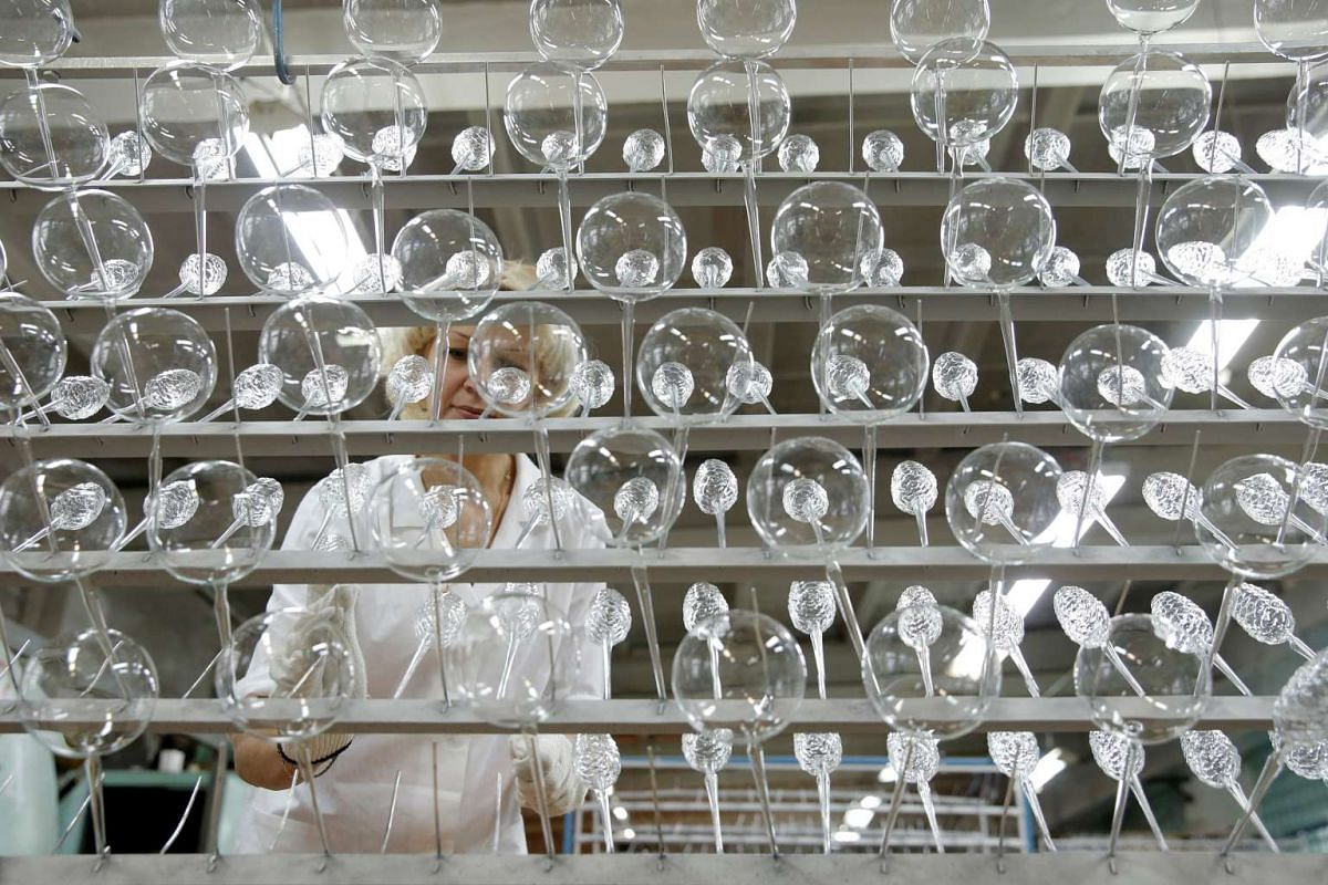 """An employee adjusts glass spheres for Christmas and New Year decorations before coating them with a layer of aluminum at the """"Yolochka"""" (Christmas tree) factory, in the town of Klin outside Moscow, Russia on Nov 24, 2016."""
