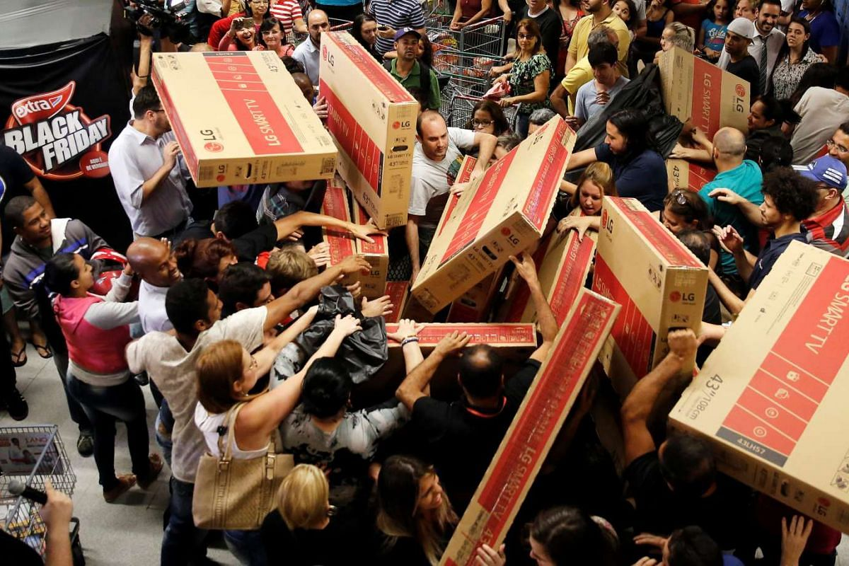 Shoppers reach for television sets as they compete to purchase retail items on Black Friday at a store in Sao Paulo, Brazil on Nov 24, 2016.