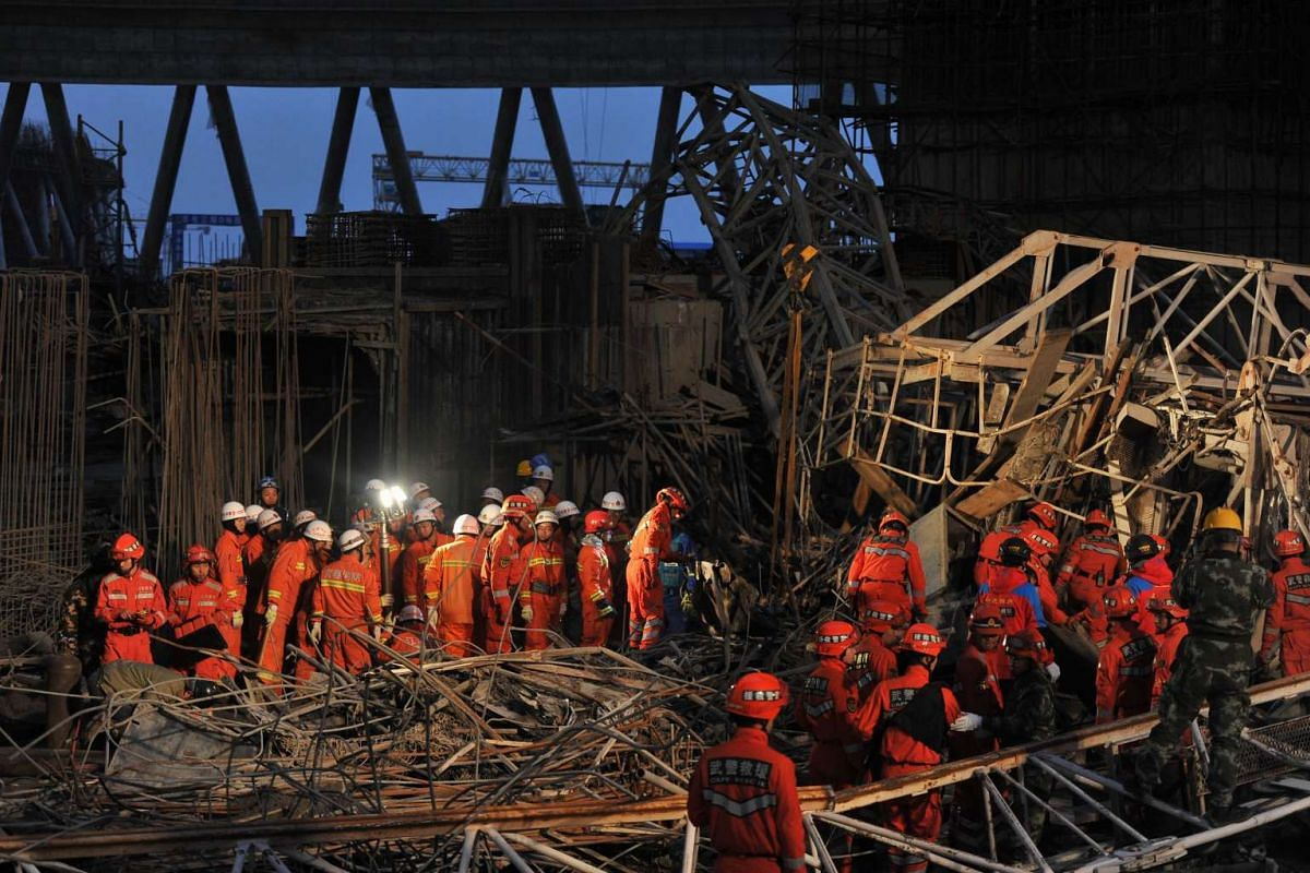 Workers search through the remains of a collapsed platform in a cooling tower at a power station at Fengcheng in China's Jiangxi province on Nov 24, 2016.