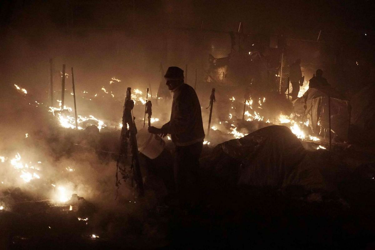 People try to extinguish fires with buckets at the moria migrants camp on the island of Lesbos early on Nov 25, 2016.