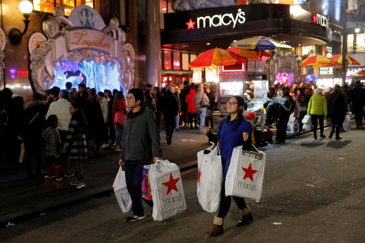 Shoppers exit Macy's Herald Square store during early opening for Black Friday sales in Manhattan, New York, US, on Nov 24, 2016.