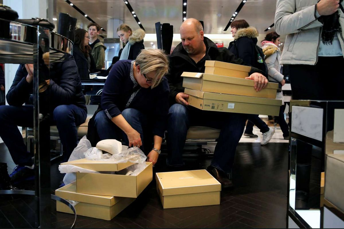 Mrs Carol Olsen tries on shoes as her husband Dave Olsen waits during early opening for Black Friday sales at Macy's Herald Square in Manhattan, New York, US, on Nov 24, 2016.