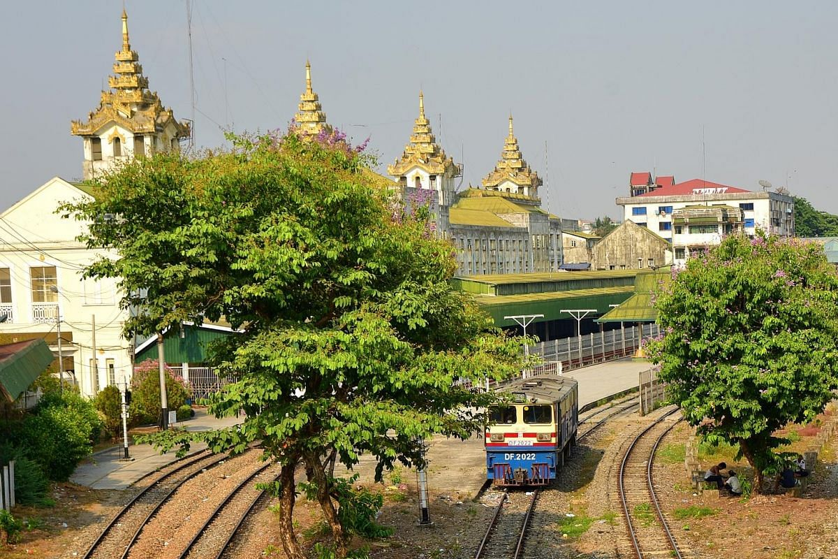 Above: The gold towers of Yangon Central Railway Station. Left: Tens of thousands of people a day use the circular train as it is the cheapest way to get around the city. Below: Snacks are sold at station platforms on Yangon's circular railway.