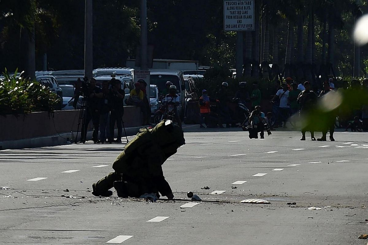 A member of the police bomb disposal unit inspects a suspicious package after detonation , along Roxas boulevard near the US embassy in Manila on Nov 28, 2016.
