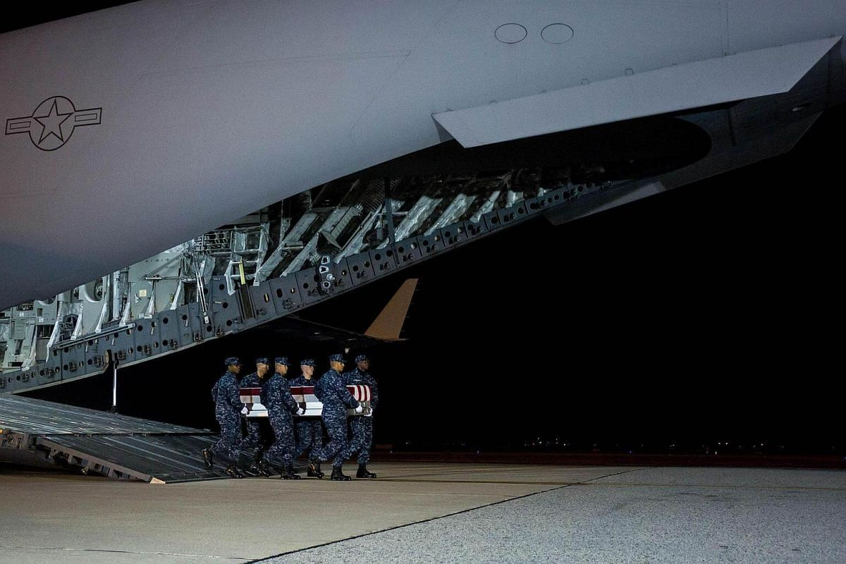 Members of a US Navy carry team move the transfer case of US Navy Senior Chief Petty Officer Scott C. Dayton during a dignified transfer on Nov 27, 2016.