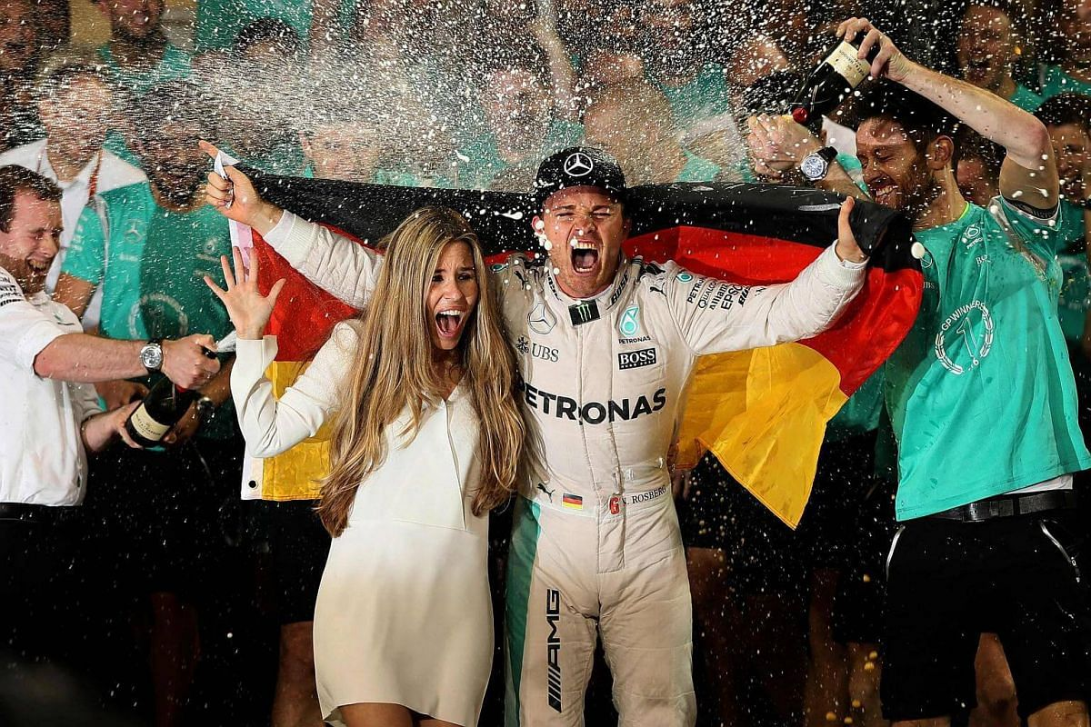 Staff members of Mercedes spray German driver Nico Rosberg (centre right) and his wife Vivian Sibold with champagne as they celebrate at the end of the Abu Dhabi Grand Prix at the Yas Marina circuit on Nov 27, 2016.