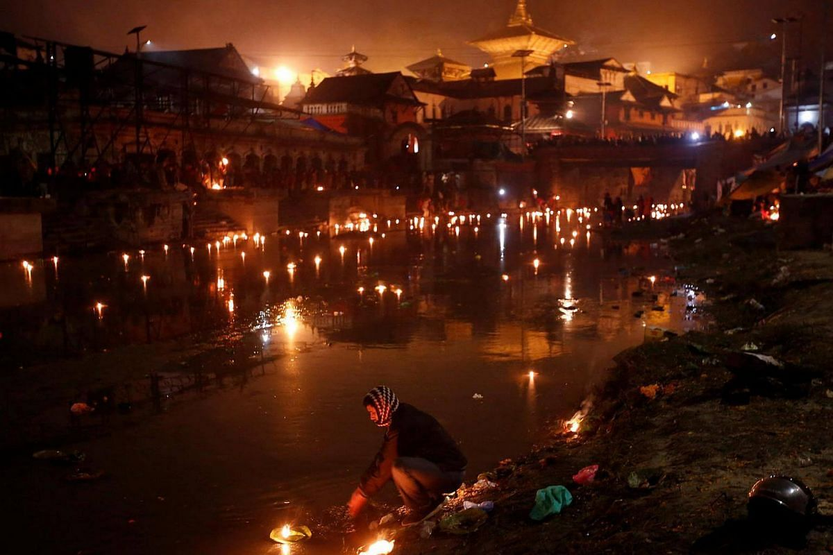 A devotee (centre) performs a religious ritual on the bank of the Bagmati River, which flows through the premises of the Pashupatinath Temple, during the Bala Chaturdashi festival in Kathmandu, Nepal on Nov 28, 2016.