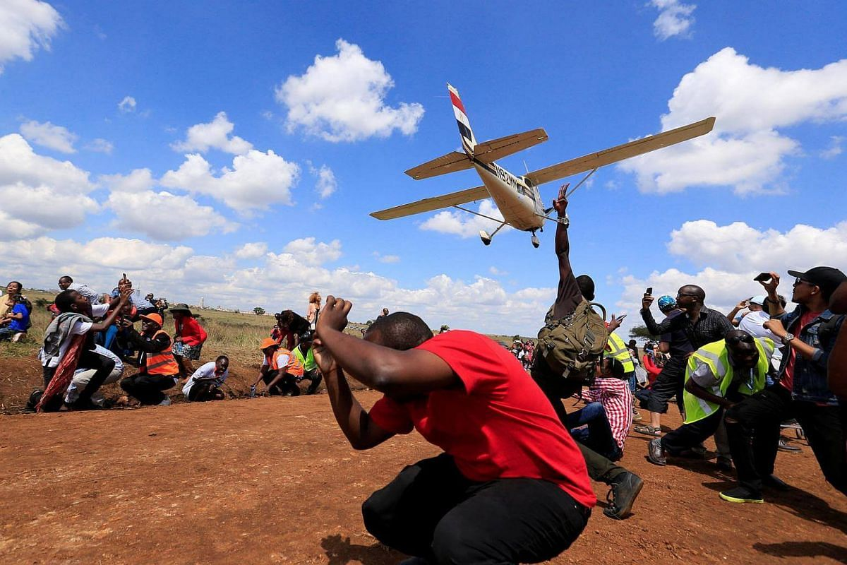 Spectators react as a plane flies over them during the Vintage Air Rally at the Nairobi national park in Kenya's capital on Nov 27, 2016.