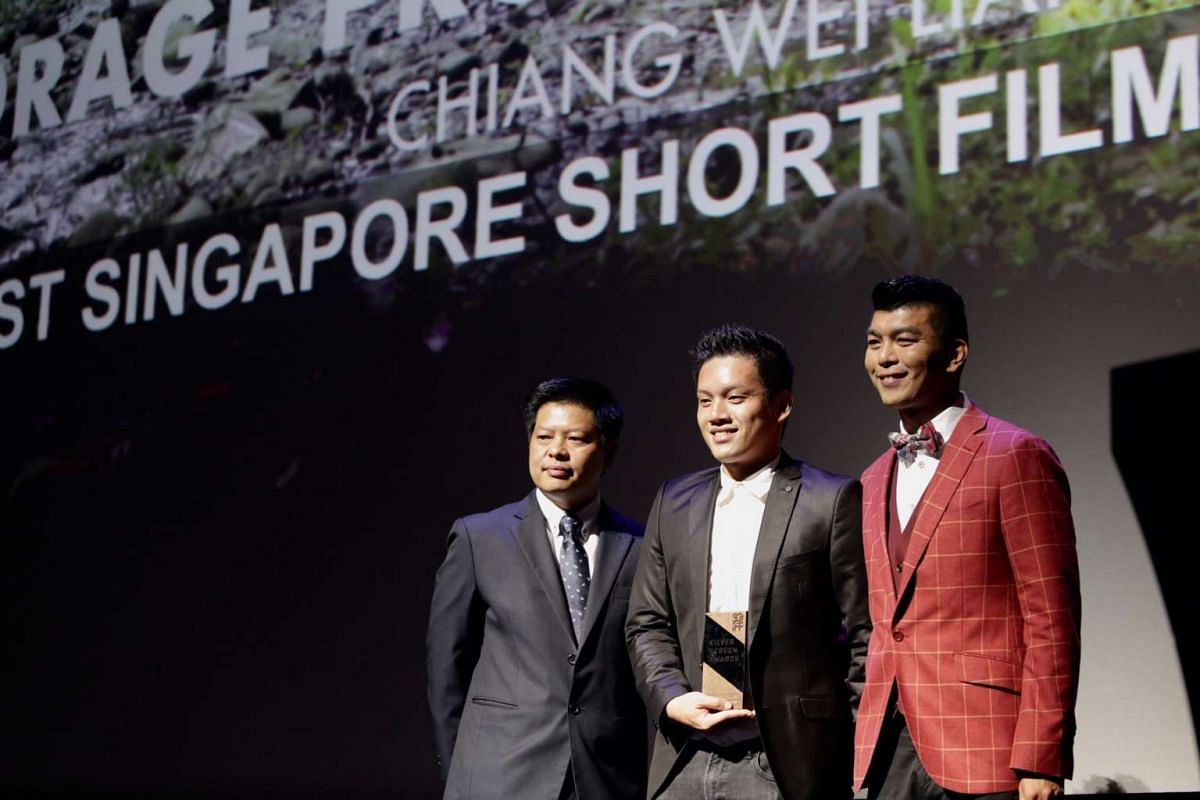 Director Royston Tan (right) and Mr Joachim Ng (left), director from Singapore Film Commission, present the award for Best Singapore Short Film to assistant director Khoo Chia Meng for Anchorage Prohibited.