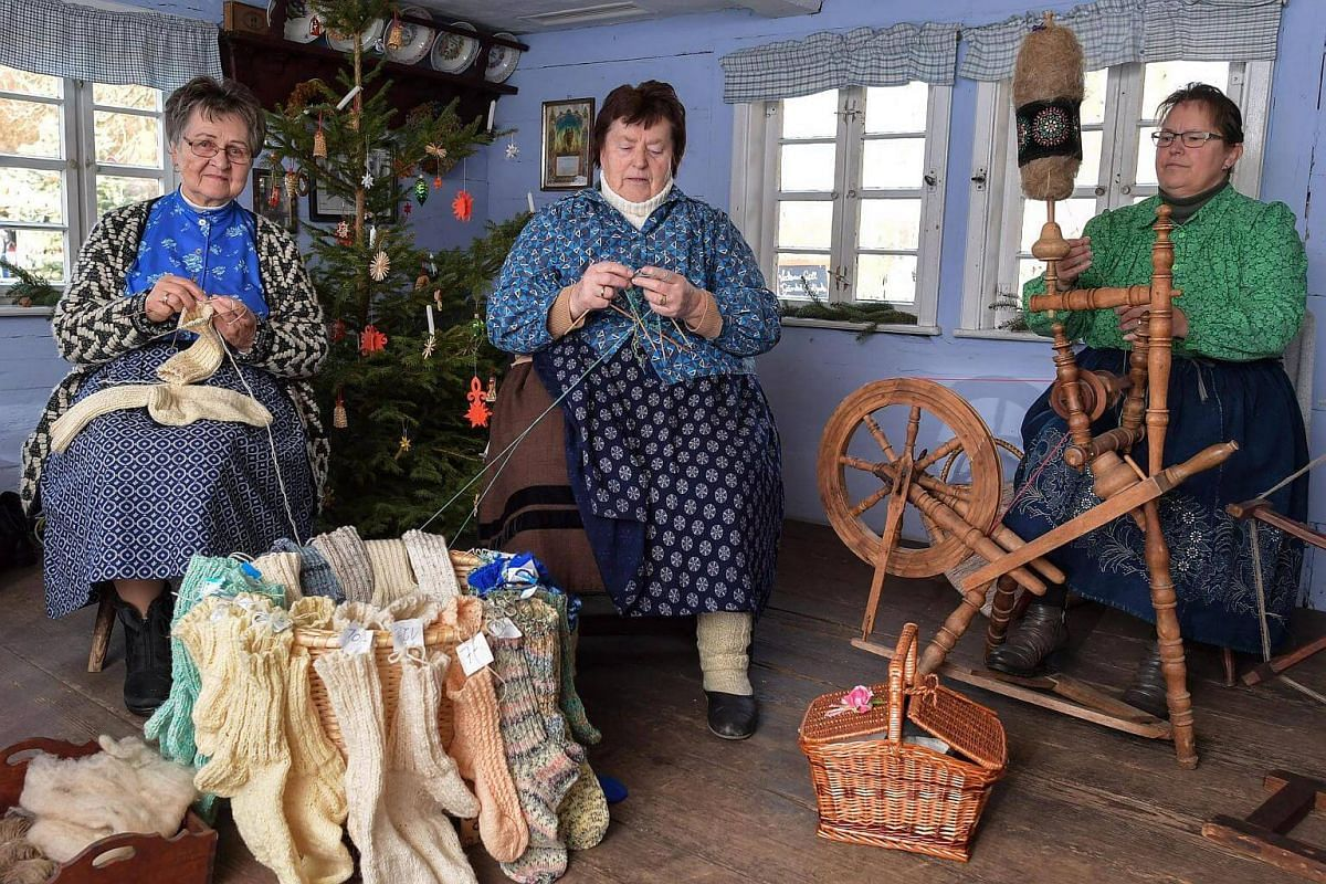 Women in traditional Sorbian-Wendish clothing, knitting socks at a Christmas market during the Spreewald Christmas festival at the historical museum village of Lehde, Germany, on Dec 3, 2016.