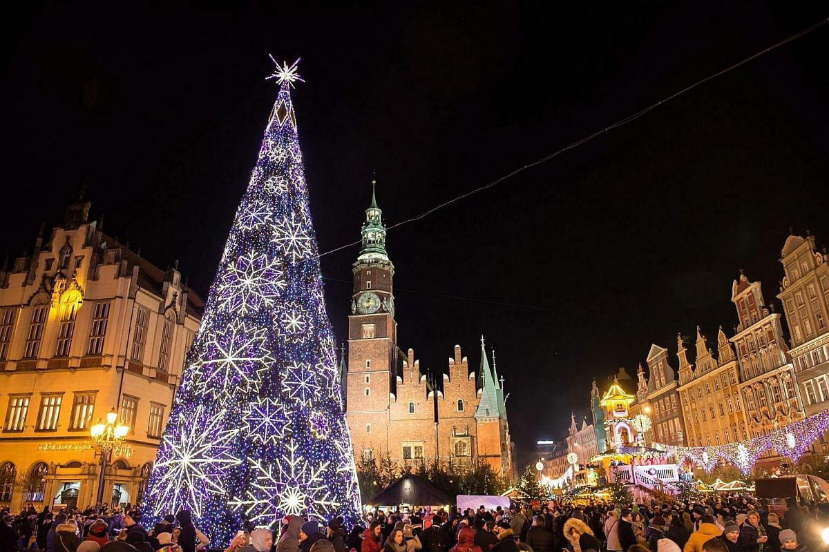 Visitors admiring the illuminated Christmas tree at the Market Square in Wroclaw, Poland, on Dec 2, 2016.