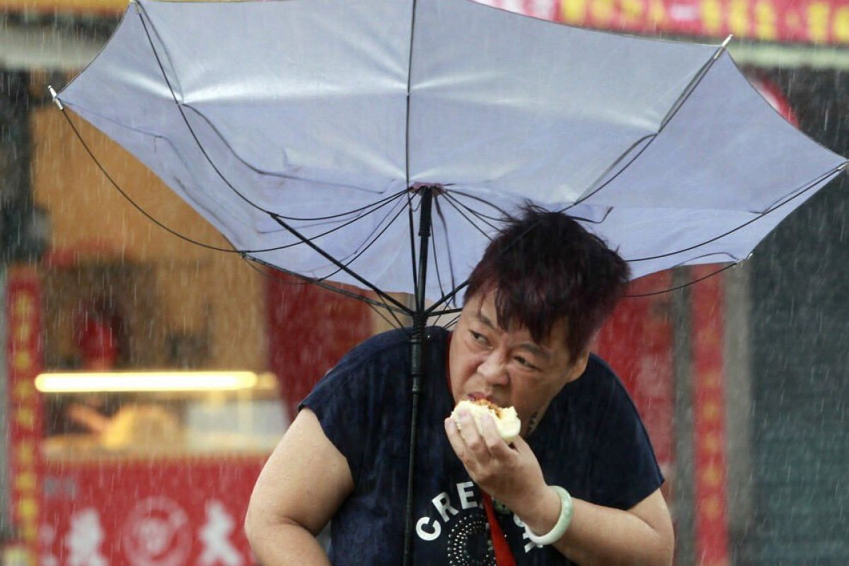 Internet sensation Mrs Dai, who continued eating her bun despite being in the middle of a typhoon.