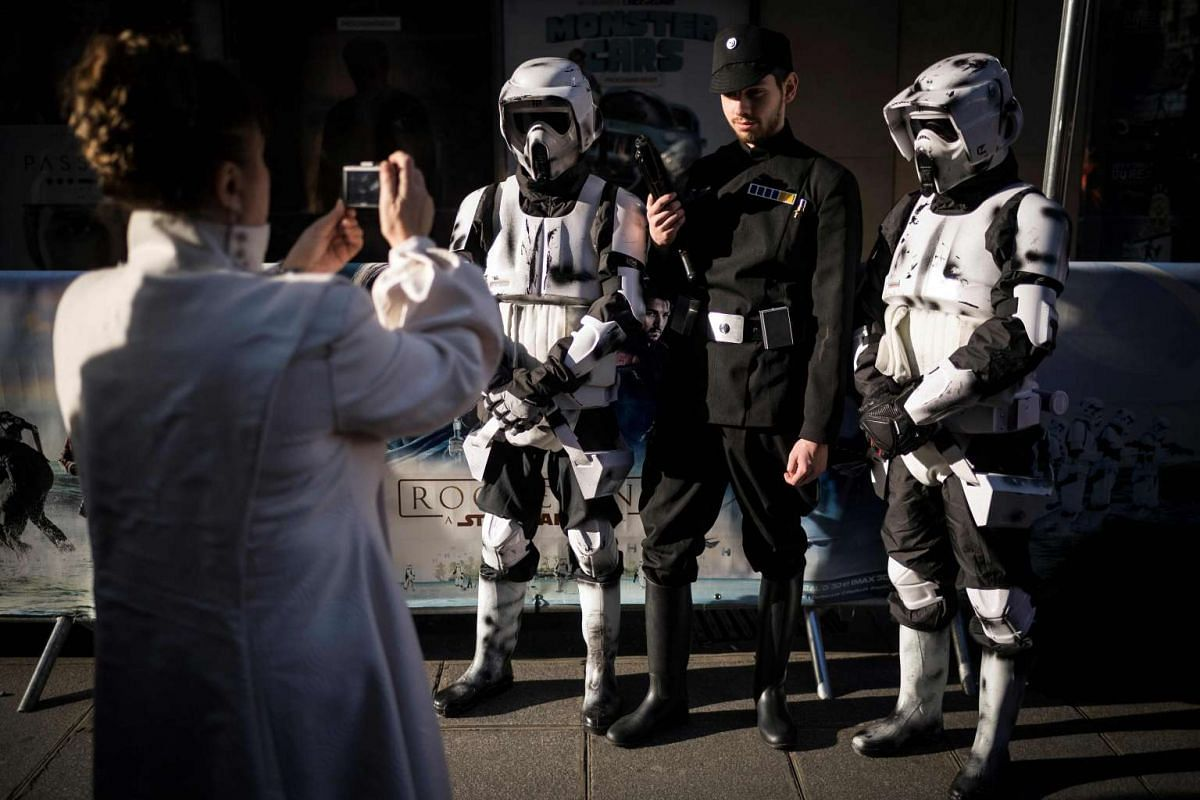 Princess Leia puts down her Blaster Pistol and picks up a camera to help snap a photo of fellow fans at the Grand Rex cinema in Paris, France, on the first day of the European release of Rogue One: A Star Wars Story on Dec 14, 2016.
