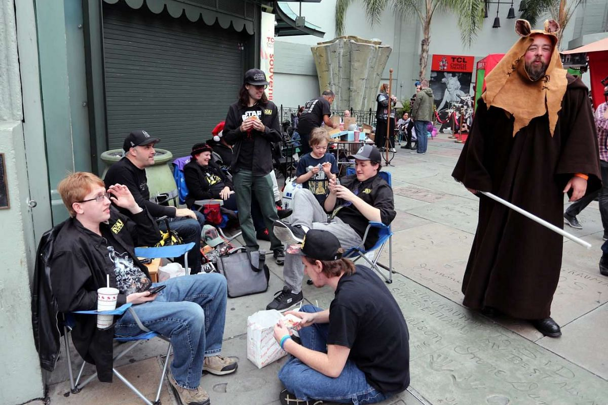 Moviegoers waiting to catch Rogue One: A Star Wars Story at the TCL Chinese Theatre in Hollywood, California, on Dec 15, 2016, watching fully-dressed fans walk past.