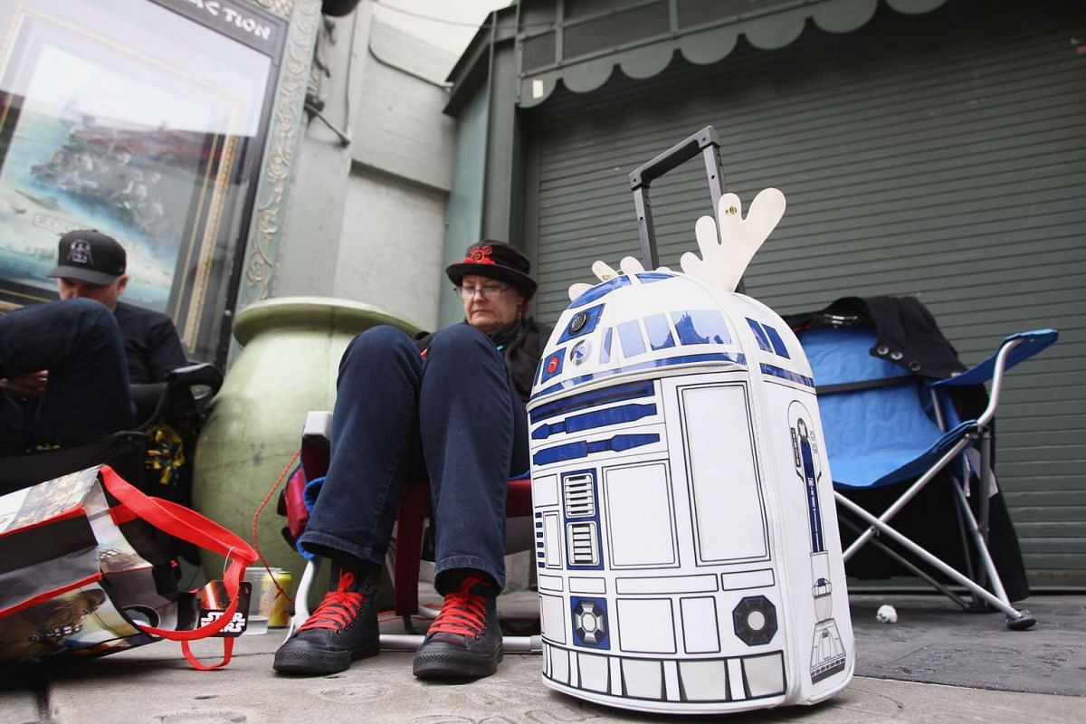 A fan with her R2-D2 on wheels queueing to catch Rogue One: A Star Wars Story at the TCL Chinese Theatre in Hollywood, California, on Dec 15, 2016.