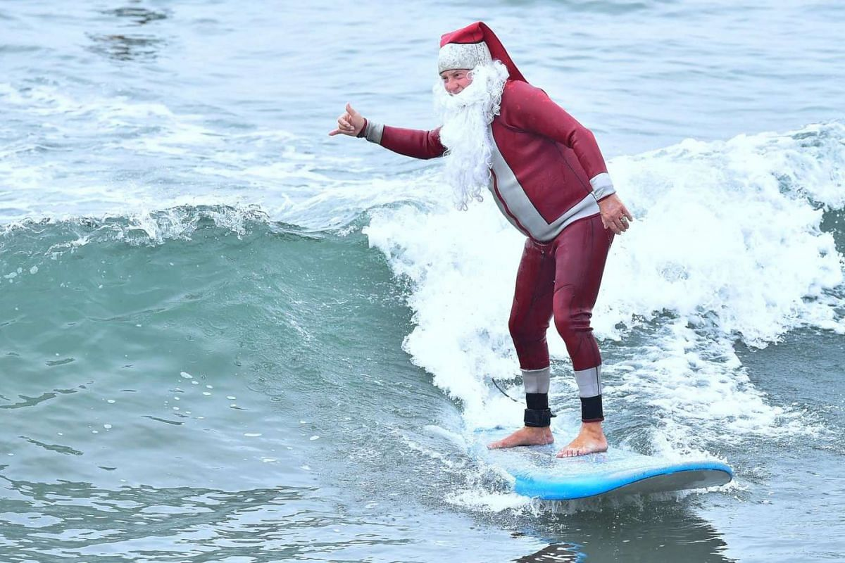 American Michael Pless, also known as Surfing Santa, at Seal Beach, California. He has gone out to ride the waves every December in his Santa Claus outfit since the 1990s.