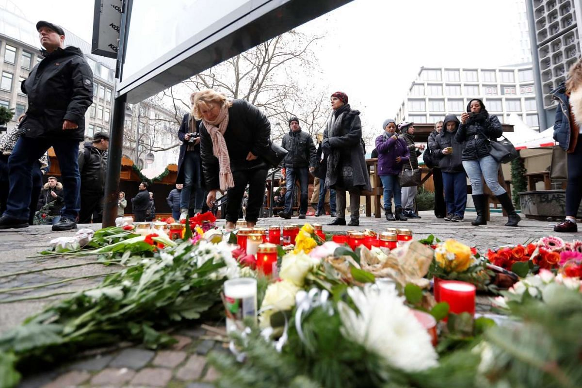 People gather to lay down flowers outside the Gedächniskirche near the area where the truck ploughed into a Christmas market.