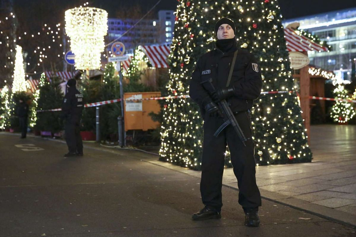 Policemen standing guard at the scene where the truck crashed into the Christmas market.