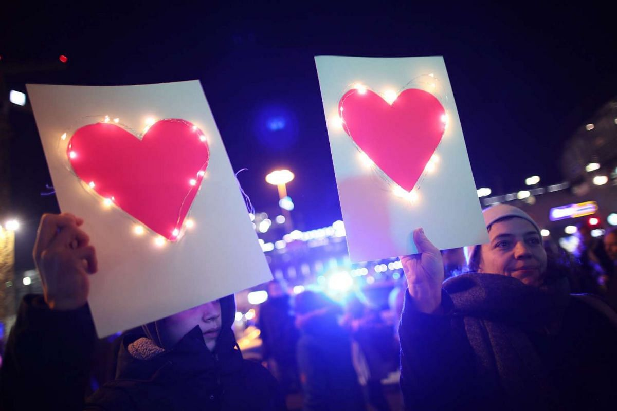 """Participants of a counter-protest against the a march of the NPD Berlin and right-wing platform """"Berlin wehrt sich!"""" (lt.""""Berlin defends itself!"""") are holding up papers with hearts at Hardenbergplatz in Berlin, Germany, December 21, 2016. PHOTO: EPA"""