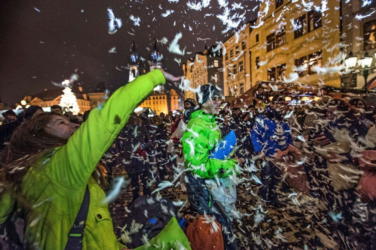 Young people enjoy a pillow fight at the Old Town Square in Prague, Czech Republic, December 22, 2016. PHOTO: EPA