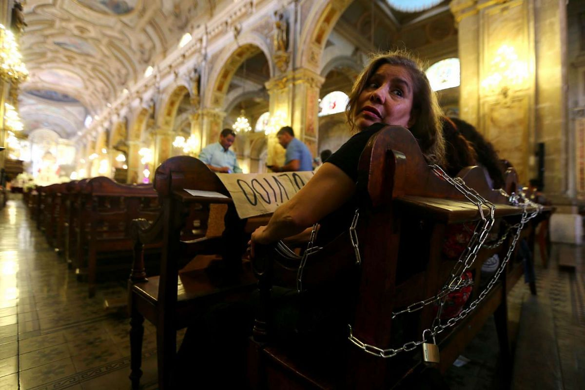 "Relatives of victims of human rights abuses during the former dictatorship of Augusto Pinochet chain themselves to pews at the Cathedral of Santiago to protest against a mass taking place in the special prison for human right abusers called ""Punta Pe"