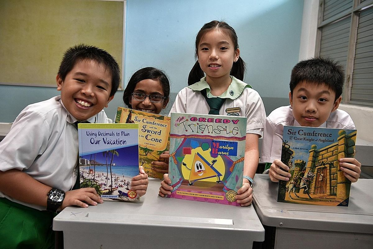 Primary 4 pupils (from left) Tan Hai Yang, Vasudevan Suresh Megna, Ellyse Wong and Bryan Pak with some of the storybooks used in class for Woodgrove Primary School's literature-based approach to maths.