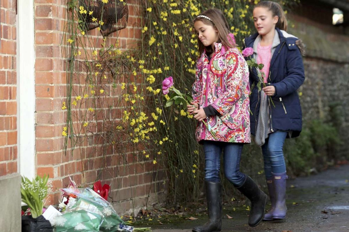 Two girls carry flowers to the house of singer George Michael, where he died on Christmas Day, in Goring, southern England, Britain on Dec 26, 2016.