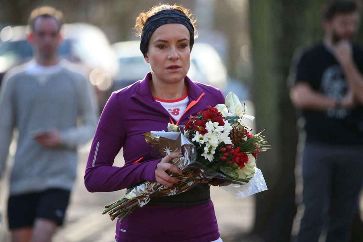 A woman brings a bouquet of flowers to the north London home of British singer George Michael on Dec 26, 2016.