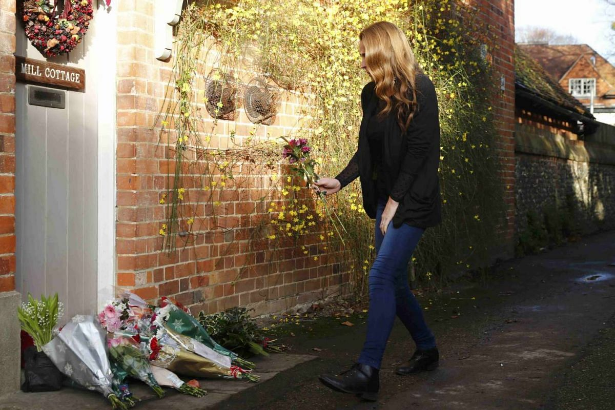 A woman carries flowers to the house of singer George Michael, where he died on Christmas Day, in Goring, southern England, Britain on Dec 26, 2016.