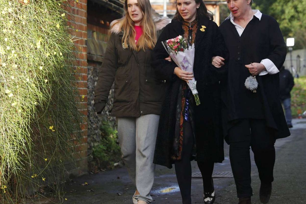 Women carry flowers to the house of singer George Michael, where he died on Christmas Day, in Goring, southern England, Britain on Dec 26, 2016.