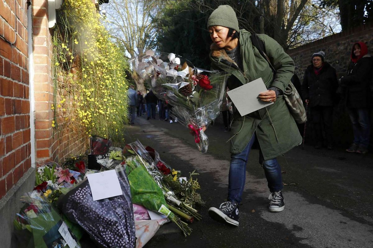 A woman carries flowers to the house of singer George Michael on Dec 26, 2016.