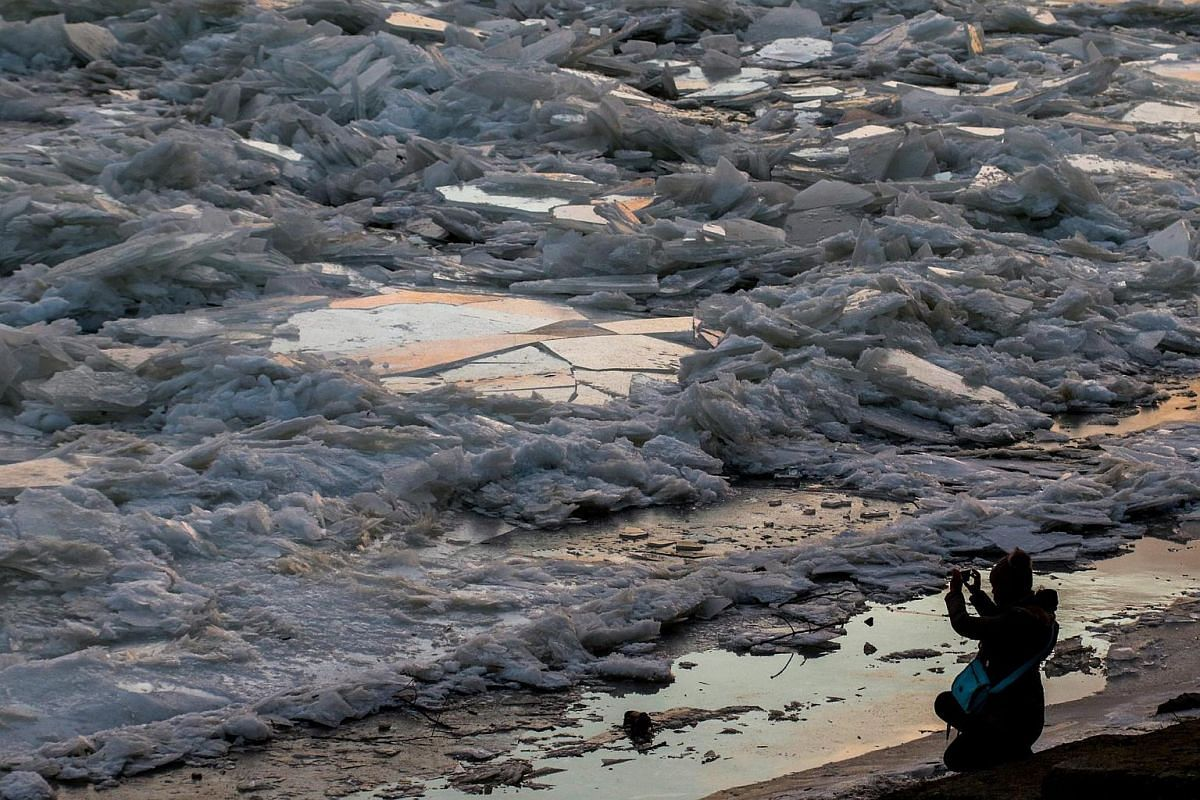 A woman takes photographs of accumulated broken ice covering the frozen surface of the River Tisza in Szolnok, 98 km southeast of Budapest, Hungary, on Jan 3, 2017.