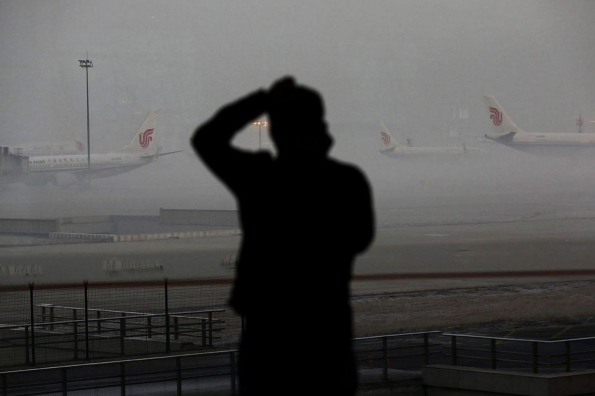 A passenger uses his mobile phone while airplanes are seen parked at Beijing Capital International Airport as heavy haze covers portions of Beijing, China, on Jan 4, 2017.