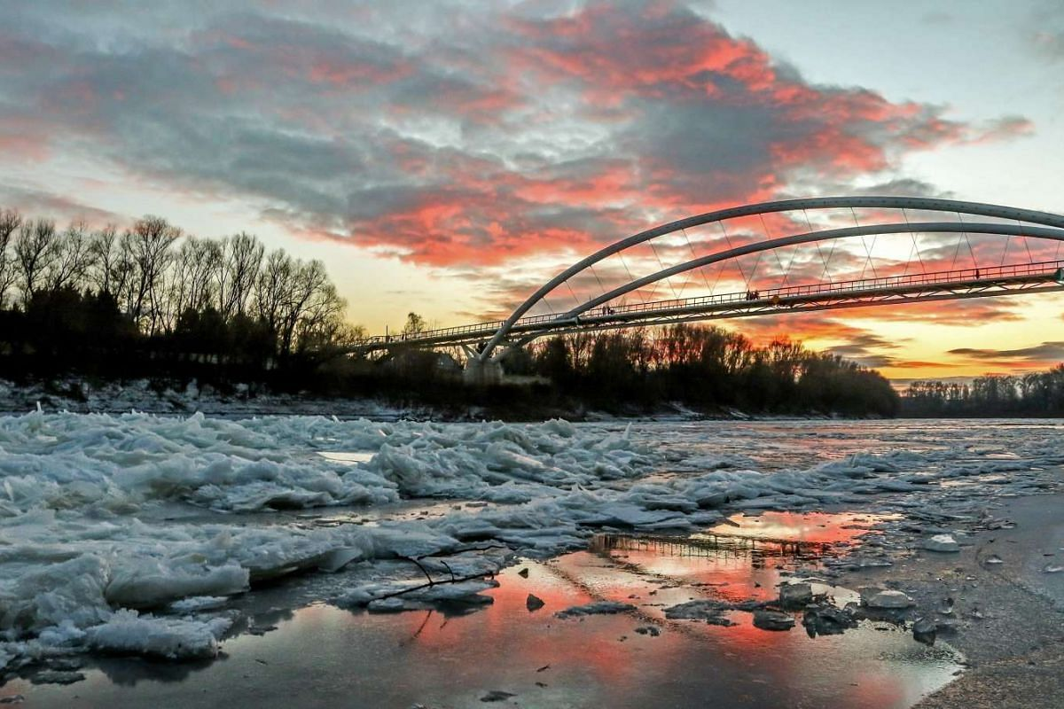 Accummulated broken ice covers the frozen surface of the River Tisza as people pass over the Tiszavirag footbridge in Szolnok, Hungary on Jan 3, 2017.